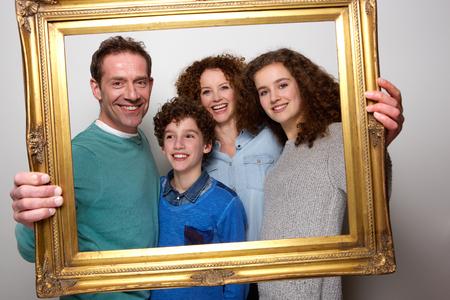 Photo pour Portrait of a happy family holding picture frame and smiling - image libre de droit