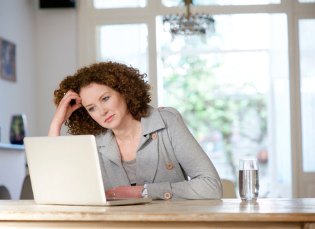 Foto de Portrait of an attractive older woman looking at laptop at home - Imagen libre de derechos