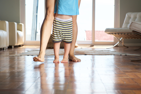 Photo for Mother walking with little boy at home on wood floor - Royalty Free Image