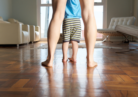 Photo pour Mother and little boy feet standing on wood floor at home - image libre de droit