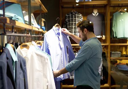 Foto de Portrait of a young man shopping for clothes at store - Imagen libre de derechos