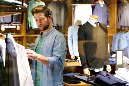 Foto de Portrait of a young man looking at clothes to buy at shop - Imagen libre de derechos