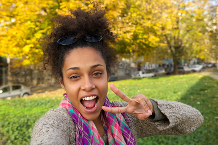 Photo pour Selfie portrait of a happy woman with showing peace sign - image libre de droit