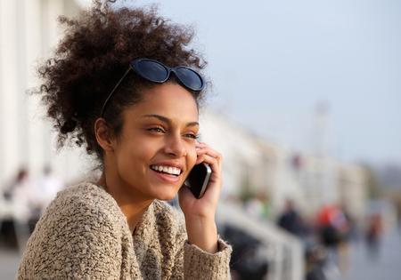 Foto de Close up portrait of an attractive young woman smiling and talking on mobile phone - Imagen libre de derechos