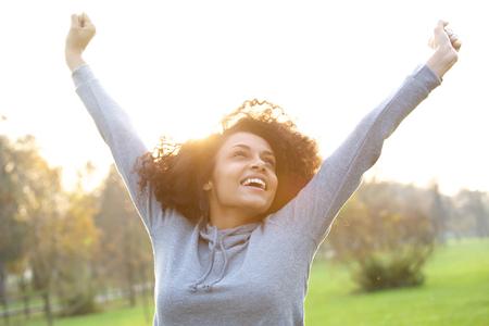 Foto de Portrait of a cheerful young woman smiling with arms raised - Imagen libre de derechos