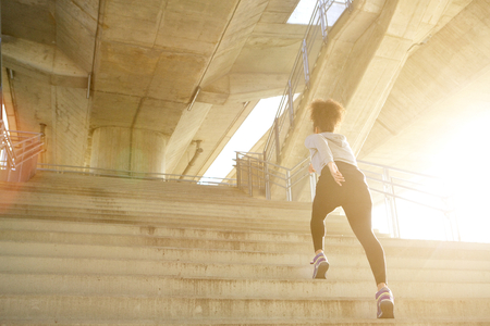 Photo pour Young exercise woman running alone up stairs - image libre de droit