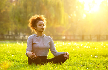 Photo pour Young african american woman meditating in nature - image libre de droit