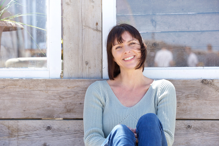 Foto de Close up portrait of a happy middle aged woman smiling outdoors - Imagen libre de derechos