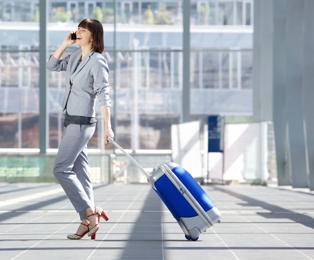 Photo pour Full length side portrait of a happy business woman walking with suitcase and talking on mobile phone at airport - image libre de droit