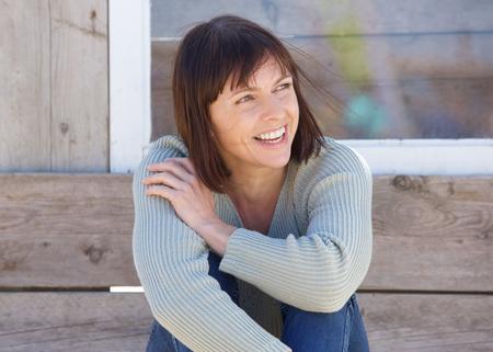 Foto de Close up portrait of a natural older lady smiling outside - Imagen libre de derechos