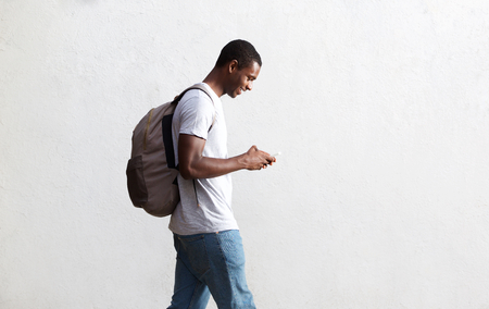 Photo pour Side view portrait of a african american student walking with bag and mobile phone - image libre de droit