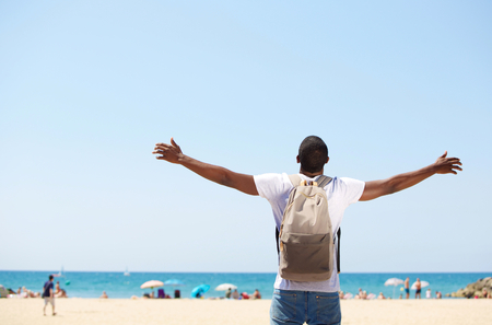 Photo pour Young african american man standing with arms spread open at beach - image libre de droit
