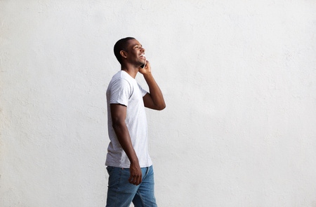 Photo pour Side view portrait of a smiling african american guy walking and talking on mobile phone - image libre de droit