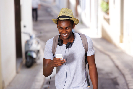 Photo pour Portrait of a happy young african american man walking in town with mobile phone - image libre de droit