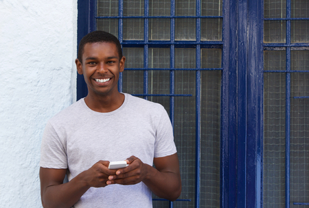Photo for Portrait of a smiling guy holding mobile phone outside - Royalty Free Image