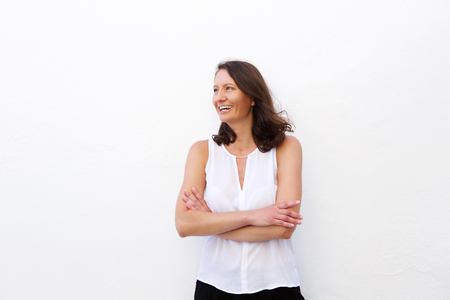 Foto per Cheerful older woman laughing with arms folded against white background - Immagine Royalty Free