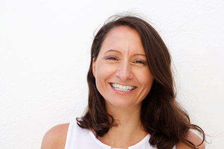 Photo pour Close up portrait of a smiling mid adult woman posing against white background - image libre de droit