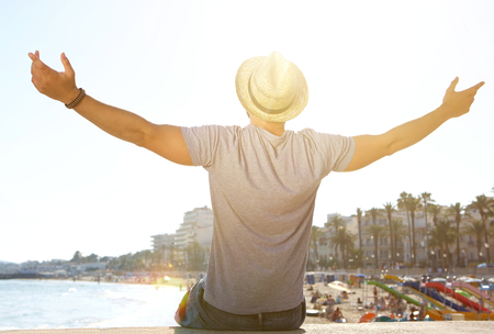 Foto de Portrait from behind of a man sitting by the beach with arms outstretched - Imagen libre de derechos