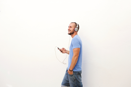 Photo for Happy man walking with mobile phone listening to music on headphones - Royalty Free Image