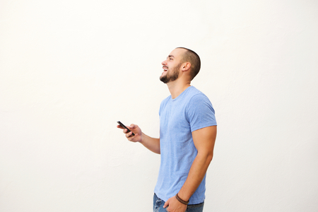 Photo for Cheerful young man walking with mobile phone against white background - Royalty Free Image