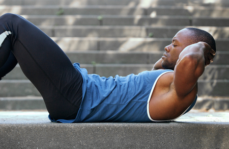 Photo for Side portrait of a fit african american man doing stomach crunches - Royalty Free Image