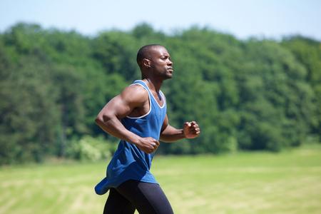 Foto de Side view portrait of a fit exercising man running outside - Imagen libre de derechos