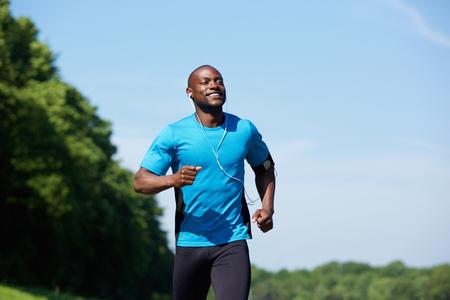 Photo pour Portrait of an active african american man running exercise workout outdoors - image libre de droit