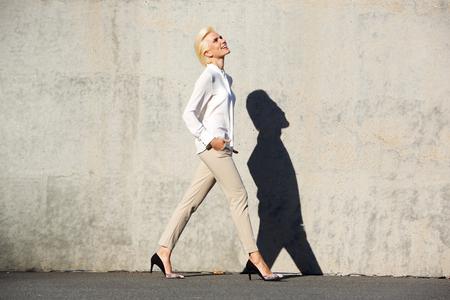 Foto de Full body side portrait of a cheerful young woman walking outside - Imagen libre de derechos