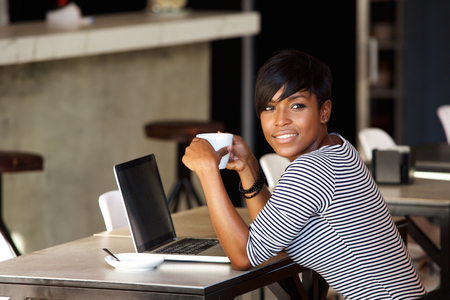 Photo pour Portrait of an african american woman relaxing at cafe with laptop and coffee - image libre de droit