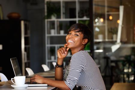 Foto de Side portrait of a smiling young african american woman sitting at cafe with laptop - Imagen libre de derechos