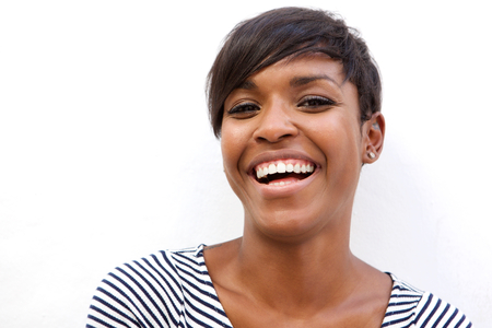 Foto de Close up portrait of a beautiful african american woman laughing on white background - Imagen libre de derechos