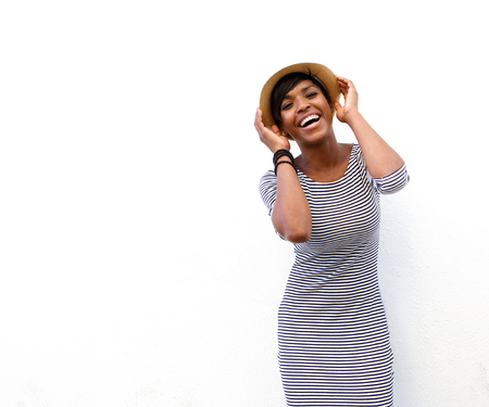 Photo pour Portrait of a smiling african american fashion model posing with hat against white background - image libre de droit