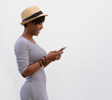 Photo for Side portrait of a smiling african american woman walking and reading text message - Royalty Free Image