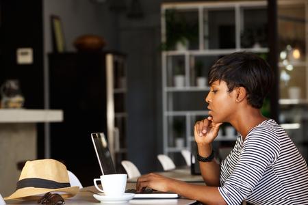 Photo pour Side portrait of an african american woman using laptop at cafe restaurant - image libre de droit