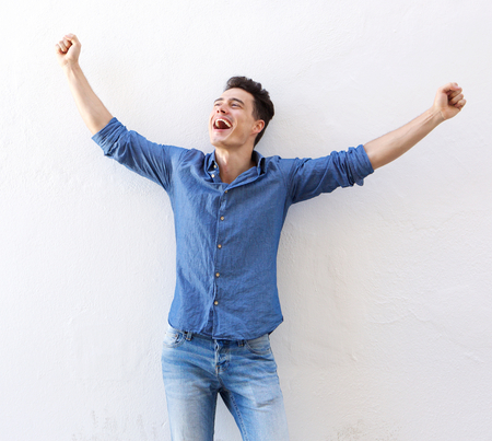 Photo pour Portrait of a cheerful young man with raised arms celebrating - image libre de droit