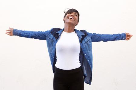 Foto de Portrait of a carefree young woman standing with arms spread open - Imagen libre de derechos