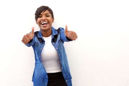 Foto de Portrait of a young woman laughing with thumbs up sign - Imagen libre de derechos