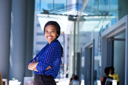 Photo pour Portrait of a smiling african business woman with arms crossed - image libre de droit