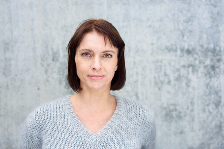 Foto de Close up portrait of a beautiful older woman with brown hair standing against gray background - Imagen libre de derechos