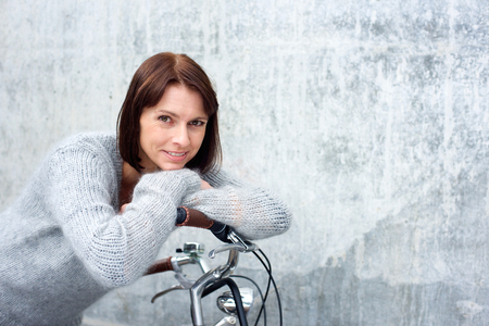 Foto per Close up portrait of an attractive older woman smiling with bike - Immagine Royalty Free
