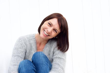 Photo pour Close up portrait of a smiling middle aged woman sitting against white wall - image libre de droit