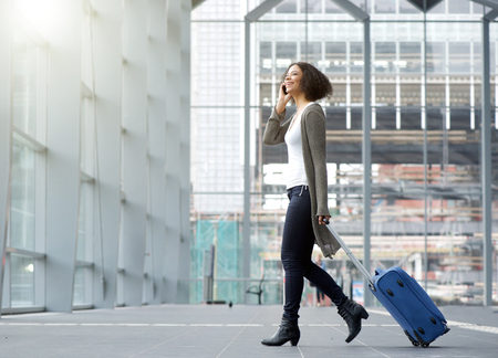 Photo for Full length side portrait of a traveling young woman with mobile phone and suitcase - Royalty Free Image