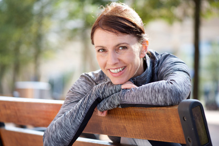 Foto für Portrait of a smiling sports woman relaxing outside on bench - Lizenzfreies Bild
