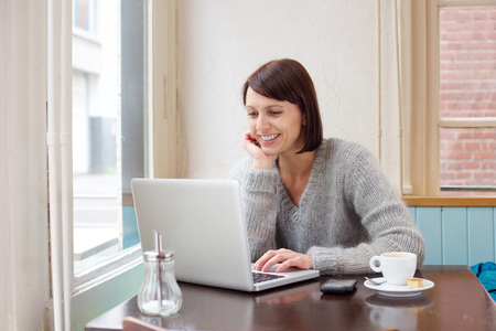 Photo for Portrait of a smiling woman sitting at cafe with laptop - Royalty Free Image