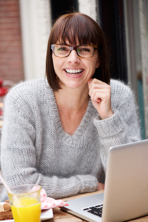 Photo for Portrait of a cheerful woman sitting with laptop outside - Royalty Free Image