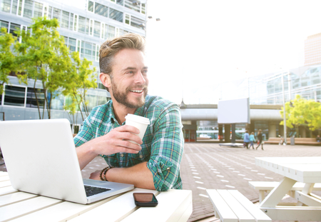Portrait of a smiling man sitting outside with laptop and coffee