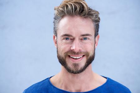 Photo pour Close up portrait man with beard smiling against gray background - image libre de droit