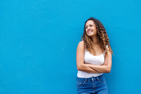 Foto de Portrait of relaxed young woman smiling with her arms crossed standing against a blue background - Imagen libre de derechos