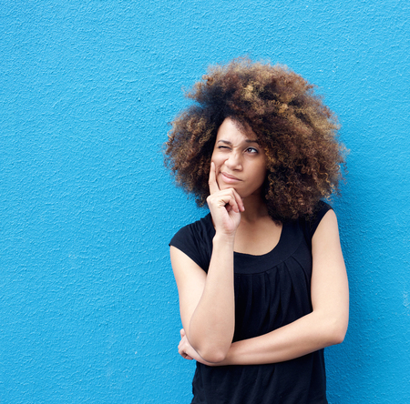 Foto de Portrait of young afro woman thinking against blue background - Imagen libre de derechos