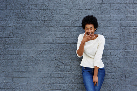 Foto de Portrait of happy african woman covering her mouth and laughing against a gray wall - Imagen libre de derechos